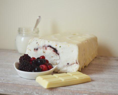 Trancio di gelato allo Yogurt variegato ai frutti di bosco, ricoperto di cioccolato bianco e granella di pistacchi. Servito a fette